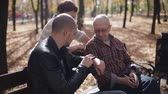 büyükbaba veya büyükanne : Elderly parents with adult son communicate in the autumn Park on a bench. The elderly man explains to parents how to use smart watch. Stok Video
