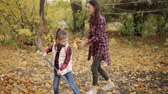 backyard : Mom and her daughter are engaged in cleaning the autumn foliage in the yard.