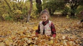 метла : The mischievous little girl merrily plays in a big pile of yellow foliage. Girl throws yellow leaves up.