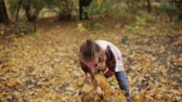 метла : A little girl puts yellow leaves in a big pile.