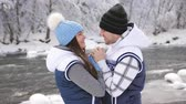 namorado : A man warms hands and kisses his girl in winter forest on the mountain river. Vídeos