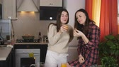 lesbianas : Two women drinking orange juice in the kitchen and feed each other fruits. Archivo de Video