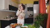 delightful : Husbands enters the kitchen to help his wife. Couple is cooking salade together. Stock Footage