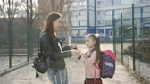 potomstvo : Mother and daughter hugging near the school after school. Dostupné videozáznamy