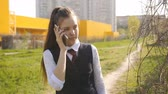 retorno : Schoolgirl comes home from school. Girl teenager talks to his mom on the phone on the way home.