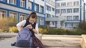 ninhada : Mom walks over and kisses teen girls near the College. Student girl sitting in the courtyard of the College and is looking for something in his backpack. Stock Footage