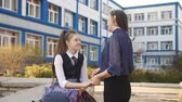 ninhada : Teenager girl talking with mom near the College. Mom and daughter teen communicate outside College after class. Stock Footage