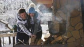 feuer frau : Happy couple preparing food in the winter outdoors near a wooden house.