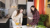 owoce : Two women drinking orange juice in the kitchen and feed each other fruits. Wideo
