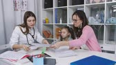 skřípat : Childrens doctor prescribes vitamins a little girl who along with her mother came to the reception in a medical clinic. The woman doctor in the Cabinet of doctor prescribes vitamins to little girl. Dostupné videozáznamy