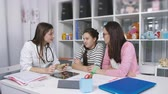 pediatrics : Examination of the patient in the office of child adolescent physician. The doctor measures the temperature of a teenage girl examination in medical clinic. Stock Footage