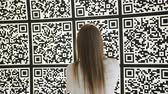 глядя : Woman using smartphone scans large QR codes on the interactive wall of the pavilion in a modern Park.