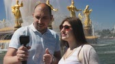 ハグ : Couple of bloggers shoot themselves and sights during the trip. Couple of bloggers from the majestic fountain in a Moscow Park.