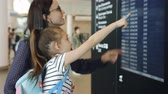 ensemble : Mother and daughter at the airport looking at the electronic scoreboard in search of information about your flight.