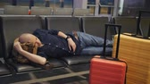 один человек : Young man sleeping while waiting the plane at airport passenger terminal. Стоковые видеозаписи