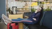 ожидая : The delay of the flight. The woman sleeps in the waiting room of the airport.