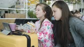ensemble : Two girls watching the tablet and drink tea with biscuits at the airport.