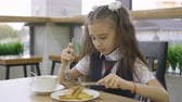 ensemble : Student elementary school in a school uniform sitting at a table in the school cafeteria and eat.