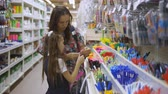 用品 : Mother and daughter in a stationery store choose school supplies. Family in supermarket chooses stationery writing pens. 動画素材