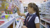 bem : Girl teenager in school uniform at the supermarket, buys a pencil for school.