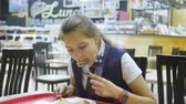 ожидая : Girl teenager having lunch in the school cafeteria. Стоковые видеозаписи