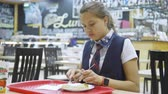 ожидая : Girl teenager in a school uniform sitting at a table in the school cafeteria and eating.
