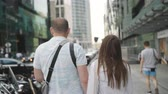 глядя : Couple in love walking in the downtown area.