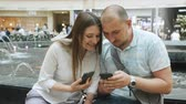 технология : Loving couple sitting near the fountain in the Mall and talking, looking at photos on the phone. Стоковые видеозаписи
