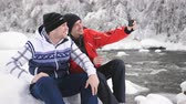 ensemble : Two cheerful men in the winter the river communicate with friends on the smartphone with video call.