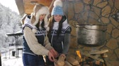 zasněžený : A couple of women cook on the grill in the yard in winter forest wooden house. Dostupné videozáznamy
