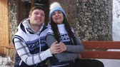 zasněžený : Man and woman having a conversation and flirting sitting on the bench near the winter Chalet in the mountains. Dostupné videozáznamy