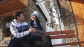 ハグ : Happy loving couple sitting on a bench near the winter Chalet in the mountains.