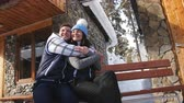 landhaus : Happy loving couple sitting on a bench near the winter Chalet in the mountains.
