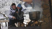 flirten : Happy couple preparing food in the winter outdoors near a wooden house.