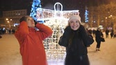 licht : The Christmas festivities in the evening in the town square. Two friends taking a walk together.