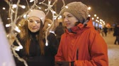 глядя : Two girls on a winter evening to view the Christmas decorations of the city.