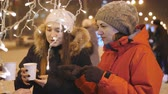noel : Two girls walk around the city on a winter evening acquire on the town square or coffee in tea cups and admiring the decoration of the city on Christmas eve. Stok Video
