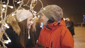 noel : Two women walk in evening winter city and view decorations, on Christmas eve. Stok Video