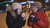 noel : Two girls winter evening in the city drinking coffee and talking. Christmas evening walk two friends. Stok Video
