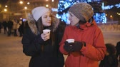 rodiny : Two girls walk on Christmas evening city, drinking coffee and talking.
