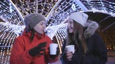 noel : Two girls on a winter evening stroll in the city centre, decorated for Christmas with bright lights and garlands. Girls drinking coffee, having fun and talking. Stok Video