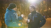 ожидая : Two friends men communicate in winter at the Christmas market and drink coffee. Стоковые видеозаписи