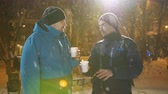 noel : Fun conversation of the two men in the town square in winter with warm coffee in hand.