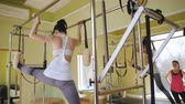 Beautiful woman doing pilates with an instructor. Physical therapy of the body. Studio equipment Pilates. Stock Footage