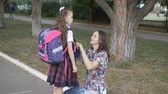 first child : Mother prepares her daughter to school. The woman straightens her jacket school uniform of my daughter on the street in front of the school. Stock Footage
