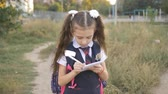 ninhada : Schoolgirl goes home through the Park after school and writes something in a notebook.