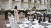 schaakstuk : Turkey, Belek - May 20, 2019. Papilon Zeugma Hotel. Mom and little daughter in nature play in big chess. Stockvideo