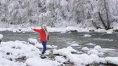 harikalar diyarı : The woman on the Bank of a mountain river and enjoys a frosty winter morning, breathes in the frosty air and rejoice. Stok Video