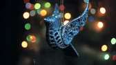 jemioła : A shiny Christmas decoration for a Christmas tree in the shape of a bird whirls around the lights of a garland