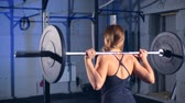 emelés : Fitness woman doing barbell squats in a gym. back view